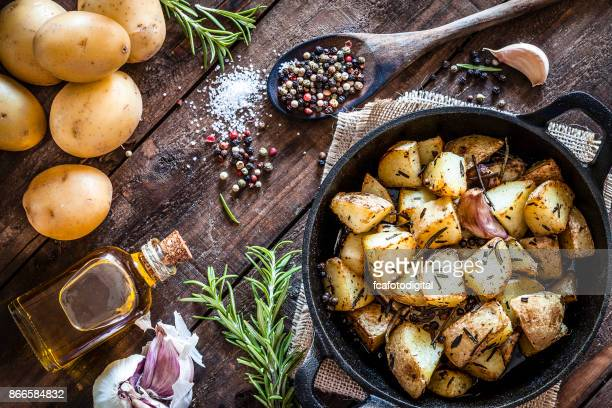 roasted potatoes on wooden kitchen table - prepared potato stock pictures, royalty-free photos & images