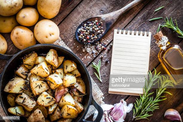 Roasted potatoes with cookbook on wooden kitchen table