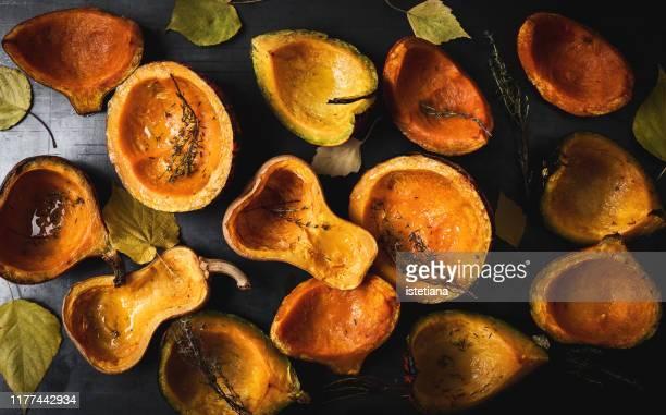 roasted pumpkins, thyme and autumn leaves - gartenkürbis stock-fotos und bilder
