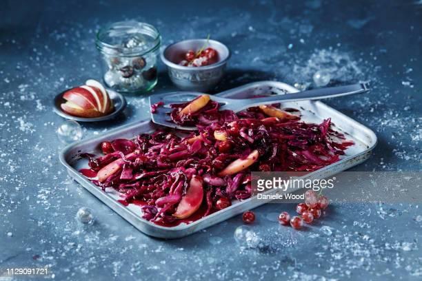 roasted red cabbage and sliced apple in baking tin, seasonal christmas food - rodekool stockfoto's en -beelden