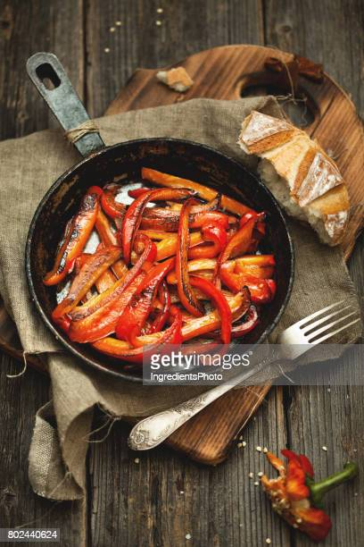 Roasted red pepper in cast iron frying pan on wooden table.