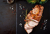 Roasted sliced Christmas ham of turkey on dark rustic background. Top view. Festival food.