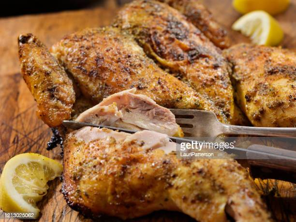 roasted spatchcock lemon chicken with roasted potatoes - carving knife stock pictures, royalty-free photos & images