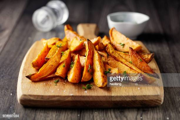 roasted sweet potatoes wedges - eating utensil stock photos and pictures