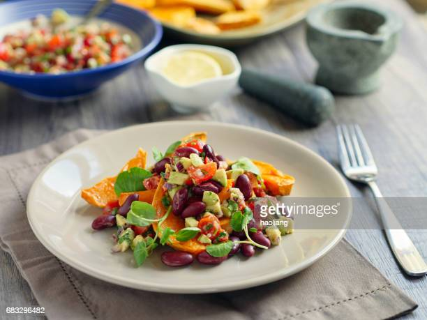 Roasted sweet potatoes wedges with guacamole and kidney beans