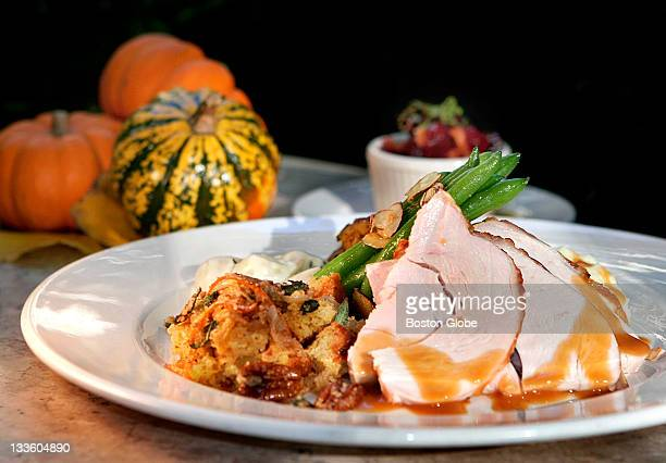 Roasted turkey breast with cornbread and candied pecan stuffing creamed onions gratine of acorn squash green beans alamadine and cranberry chutney is...