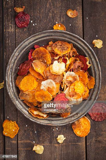 Roasted vegetable chips made of parsnips, sweet potatoes, beetroots, carrots and turnips on plate