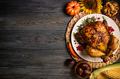 Roasted whole chicken or turkey with autumn vegetables for thanksgiving dinner on wooden background. Thanksgiving Day concept. Top view