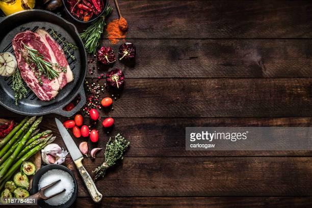 asar un filete de ternera y verduras en una parrilla de hierro con espacio de copia en la mesa - ingredient fotografías e imágenes de stock
