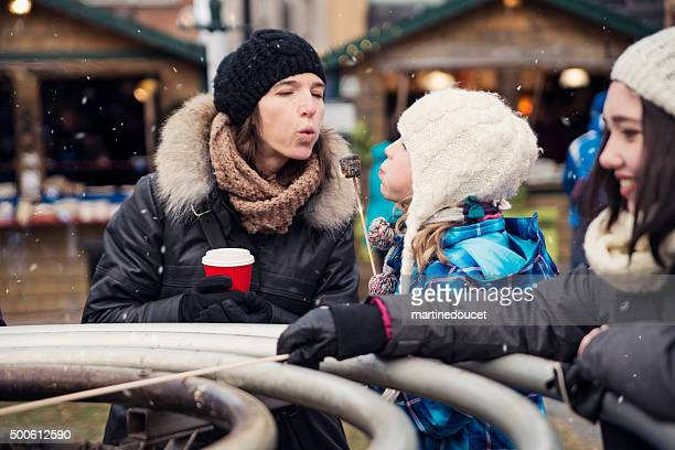 roasting marshmallow at an outdoors winter public market. - mother and daughter smoking stock photos and pictures