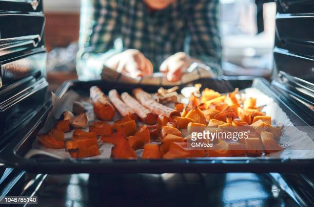 roasting pumpkins in the oven - vegetarian food stock pictures, royalty-free photos & images