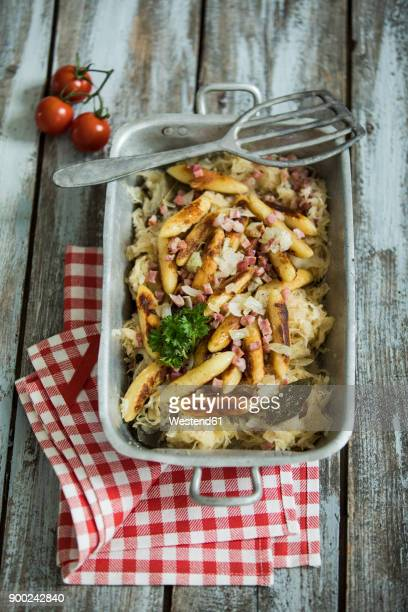 roasting tray of finger-shaped potato dumplings with sauerkraut and bacon on cloth and wood - zuurkool stockfoto's en -beelden
