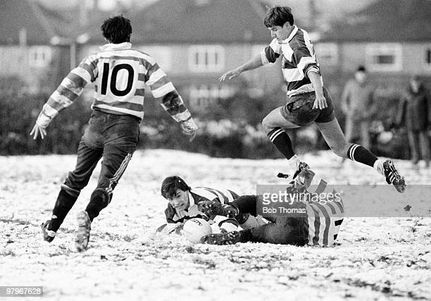 Rob Andrew of Nottingham tackles Cedric Carr of Rosslyn Park as Richard Moon of Nottingham jumps over them during the Nottingham v Rosslyn Park Rugby...