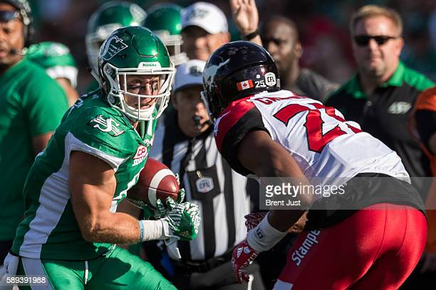 Rob Bagg of the Saskatchewan Roughriders looks to avoid Tommie Campbell of the Calgary Stampeders in first half action of the game between the...