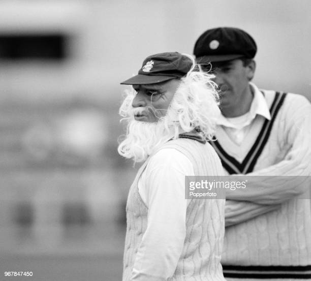 Rob Bailey of Northamptonshire looks on as teammate Allan Lamb wears a fancy dress mask during a County Championship match between Essex and...