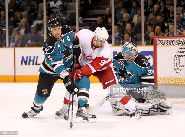 Rob Blake of the San Jose Sharks and Tomas Holmstrom of the Detroit Red Wings go for the puck while Evgeni Nabokov of the Sharks plays in the goal in...