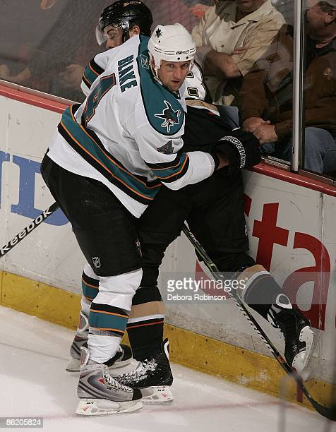 Rob Blake of the San Jose Sharks checks Andrew Ebbett of the Anaheim Ducks into the boards during Game Four of the Western Conference Quarterfinal...