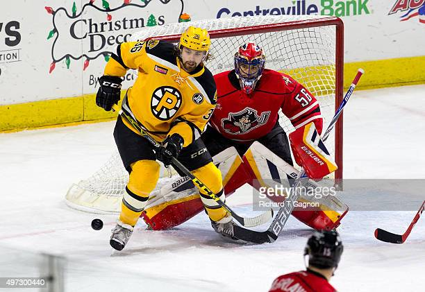 Rob Borden of the Providence Bruins and Mike McKenna of the Portland Pirates both watch the puck during an American Hockey League game at the Dunkin'...