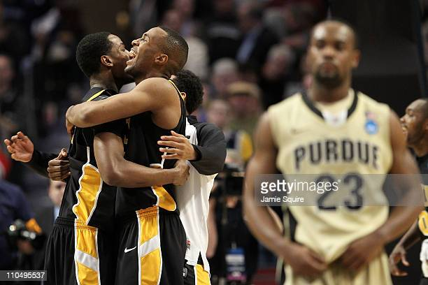 Rob Brandenberg and D.J. Haley of the Virginia Commonwealth Rams celebrate their win as Lewis Jackson of the Purdue Boilermakers walks off the court...