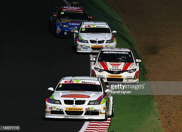 Rob Collard of Great Britain drives the ebay Motors BMW 320si ahead of Matt Neal in the Honda YUASA Racing Team Honda Civic and Tom Onslow Cole in...