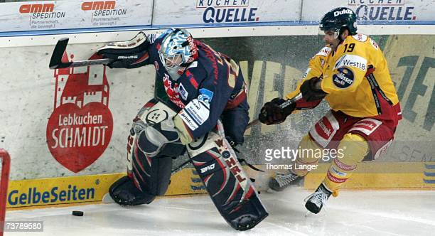Rob Collins of Dusseldorf tackles Jean-Francois Labbe of Nuremberg during the DEL Play Off semi final match between Sinupret Ice Tigers and DEG Metro...