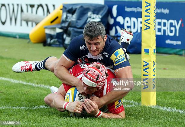 Rob Cook of Gloucester Rugby scores a try in the corner as Tom Brady of Sale Sharks tries to tackle during the Aviva Premiership match between...