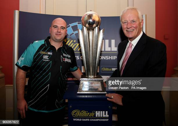 Rob Cross and Barry Hearn chairman of PDC poses with the trophy during day fifteen of the William Hill World Darts Championship at Alexandra Palace...