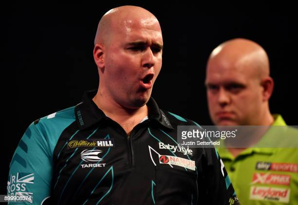 Rob Cross celebrates during his Semi Final Match as Michael van Gerwen looks on during the 2018 William Hill PDC World Darts Championships at...