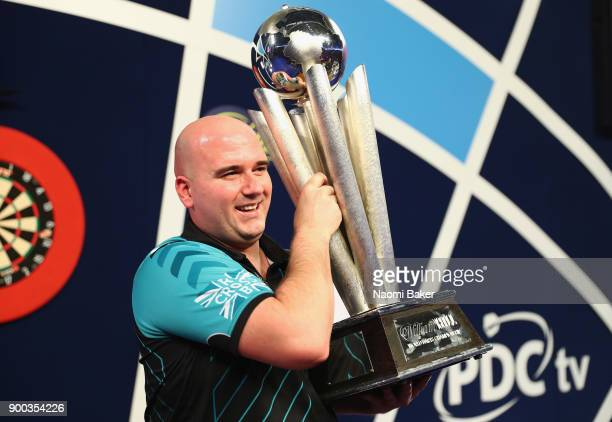 Rob Cross of England poses with the Sid Waddell Trophy after winning the PDC World Darts Championship final against Phil Taylor of England on Day...