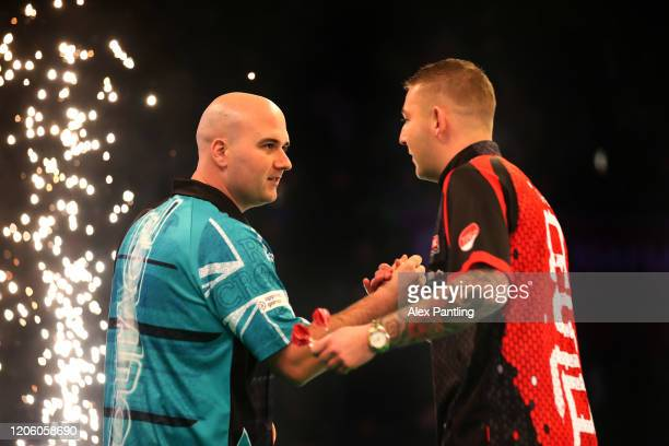 Rob Cross shakes hands with Nathan Aspinall ahead of their match during day two of the Unibet Premier League at Motorpoint Arena on February 13 2020...