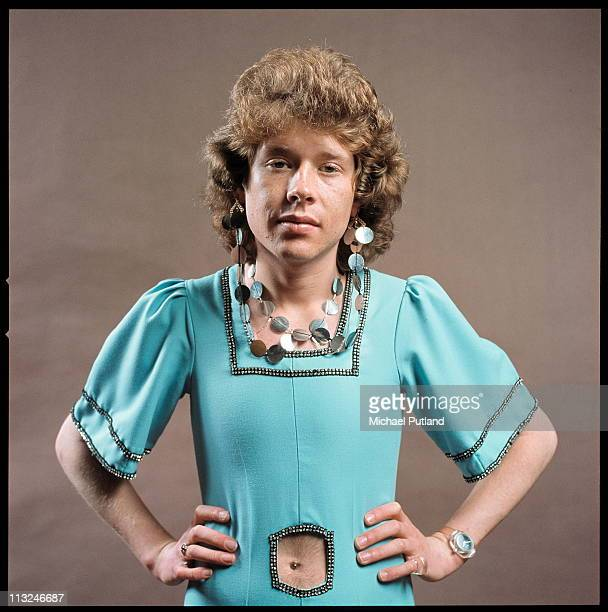Rob Davis of English glam rock band Mud studio portrait wearing dress necklace and earrings London 1975