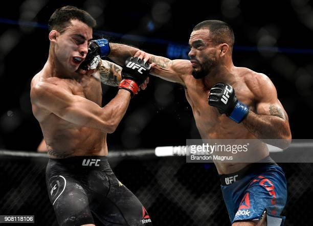 Rob Font punches Thomas Almeida of Brazil in their bantamweight bout during the UFC 220 event at TD Garden on January 20, 2018 in Boston,...