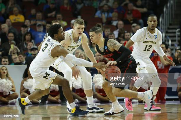Rob Gray of the Houston Cougars drives against Zavier Simpson and Moritz Wagner of the Michigan Wolverines in the second half during the second round...