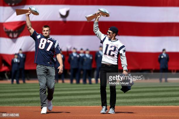 Rob Gronkowski and Tom Brady of the New England Patriots enter the field carrying Vince Lombardi trophies before the opening day game between the...