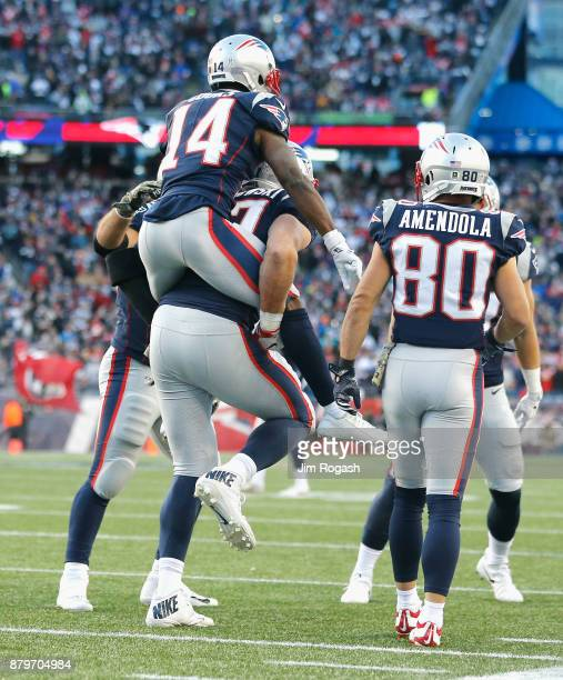 Rob Gronkowski carries Brandin Cooks of the New England Patriots after a touchdown during the fourth quarter of a game against the Miami Dolphins at...