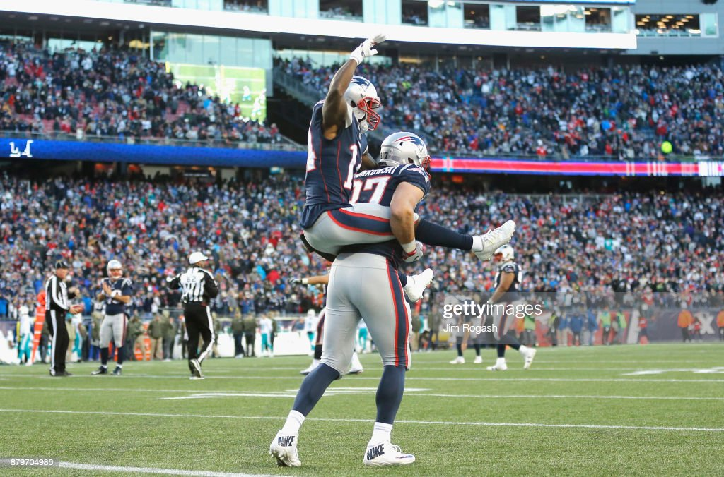 Rob Gronkowski #87 carries Brandin Cooks #14 of the New England Patriots after a touchdown during the fourth quarter of a game against the Miami Dolphins at Gillette Stadium on November 26, 2017 in Foxboro, Massachusetts.