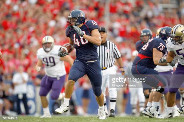 Rob Gronkowski of the Arizona Wildcats runs for a first quarter touchdown in front of Cameron Elisara of the Washington Huskies during a first...