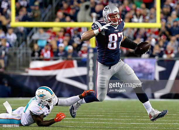 Rob Gronkowski of the New England Patriots carries the ball as he scores a touchdown during the first quarter against the Miami Dolphins at Gillette...