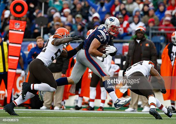 Rob Gronkowski of the New England Patriots catches a pass before being hit by TJ Ward of the Cleveland Browns in the third quarter during the game at...