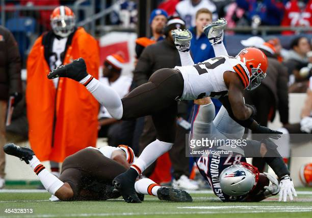 Rob Gronkowski of the New England Patriots catches a pass before being hit by TJ Ward and D'Qwell Jackson of the Cleveland Browns in the third...