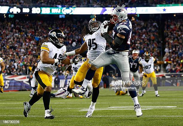 Rob Gronkowski of the New England Patriots catches a pass in front of Jarvis Jones and Troy Polamalu of the Pittsburgh Steelers in the second quarter...