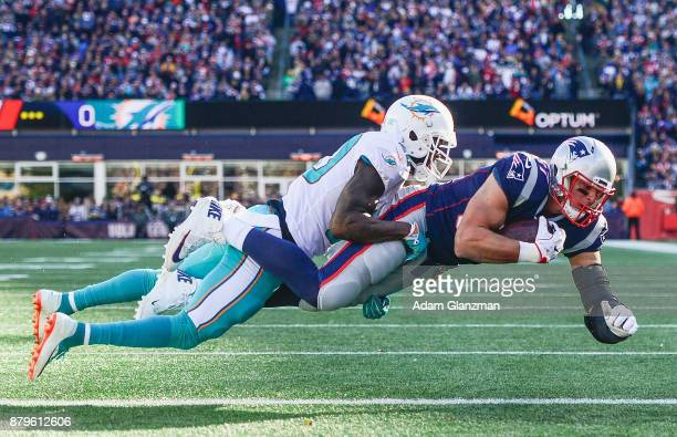 Rob Gronkowski of the New England Patriots catches a touchdown pass as he is defended by Reshad Jones of the Miami Dolphins during the first quarter...