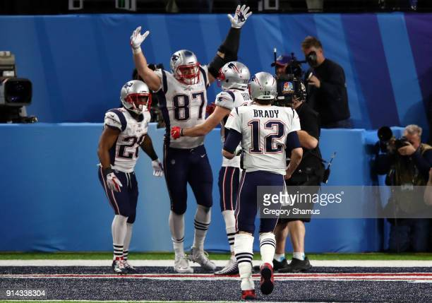 Rob Gronkowski of the New England Patriots celebrates his four yard touchdown catch with teammates James White Chris Hogan and Tom Brady during the...