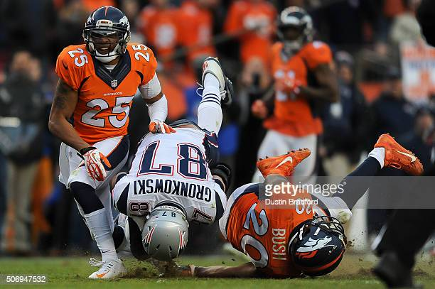 Rob Gronkowski of the New England Patriots is hit by John Bush and Chris Harris of the Denver Broncos after making a reception on a fourth down...