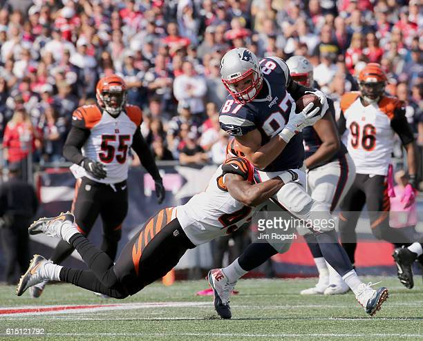 Rob Gronkowski of the New England Patriots is tackled by George Iloka of the Cincinnati Bengals during the game at Gillette Stadium on October 16...