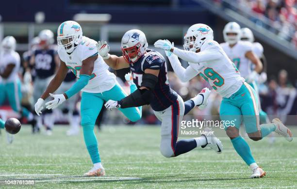 Rob Gronkowski of the New England Patriots is unable to catch a pass as he is defended by TJ McDonald and Minkah Fitzpatrick of the Miami Dolphins...