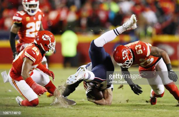 Rob Gronkowski of the New England Patriots is upended as he is tackled by Kendall Fuller and Anthony Hitchens of the Kansas City Chiefs in the first...