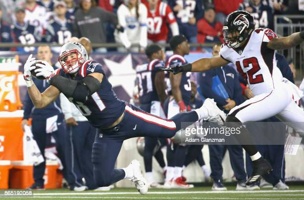 Rob Gronkowski of the New England Patriots makes a diving catch as he is defended by Duke Riley of the Atlanta Falcons during the first quarter of a...