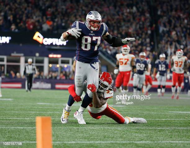 Rob Gronkowski of the New England Patriots runs the ball after making a catch as Josh Shaw of the Kansas City Chiefs defends in the fourth quarter at...