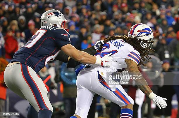Rob Gronkowski of the New England Patriots tackles Stephon Gilmore of the Buffalo Bills after Gilmore intercepted a pass during the fourth quarter at...